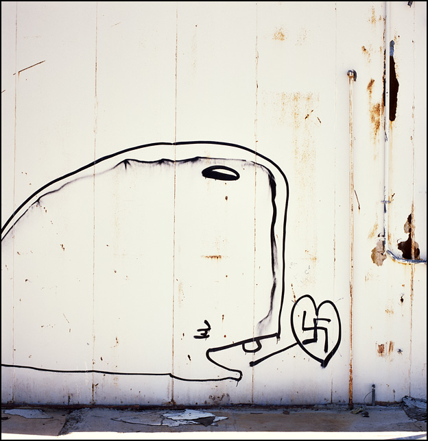 Graffiti of a sperm whale saying he loves the Nazi swastika painted on an abandoned restaurant along Interstate 40 and old Route 66 in New Mexico. The painting is by David Choe.