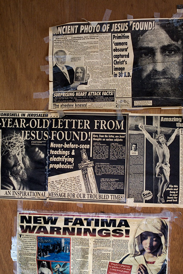 Newspaper clippings with weird religious stories from the national enquirer and the weekly world news cover a bedroom door in an abandoned house. Ancient photo of Jesus found, new Jesus mystery, crown of thorns found, letter from Jesus discovered.