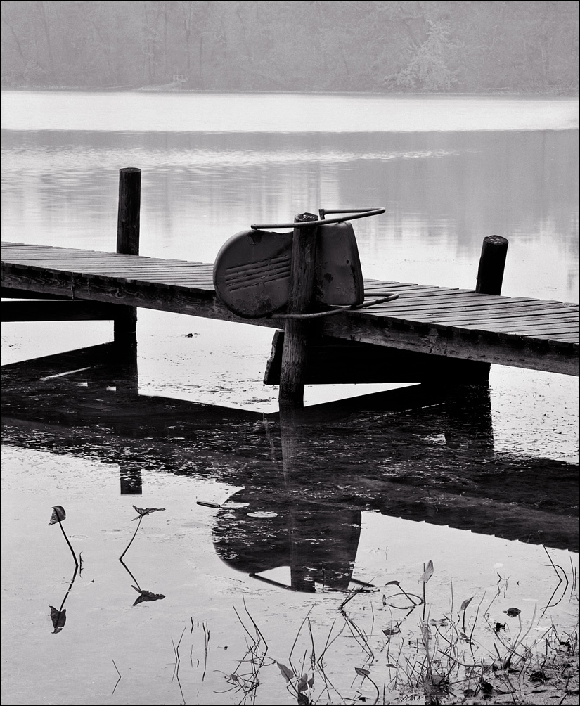 An old wooden pier with an antique metal patio chair hanging on a post and reflected in the water among the lily pads at Goose Lake in Whitley County, Indiana.