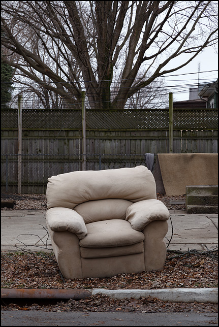 An overstuffed chair sits on the edge of the road beside an old house on Nelson Street in Fort Wayne, Indiana.