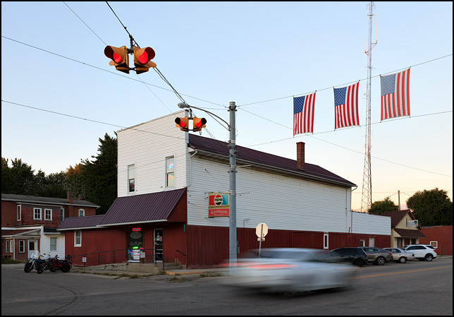 Three American flags hang over the intersection of Main Street and Market Street in the small town of New Paris, Indiana. A car speeds through the intersection past the Landmark Bar and Grille in the evening near sunset.