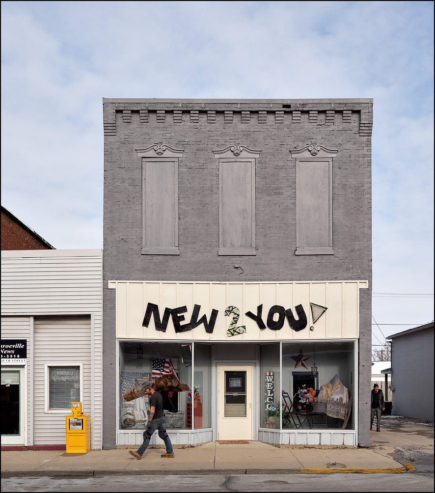 New 2 You is a secondhand shop on South Street in the small town of Monroeville, Indiana. The front windows are decorated with American flags and other patriotic items. A construction worker carrying a large piece of metal is walking past the front of the store.