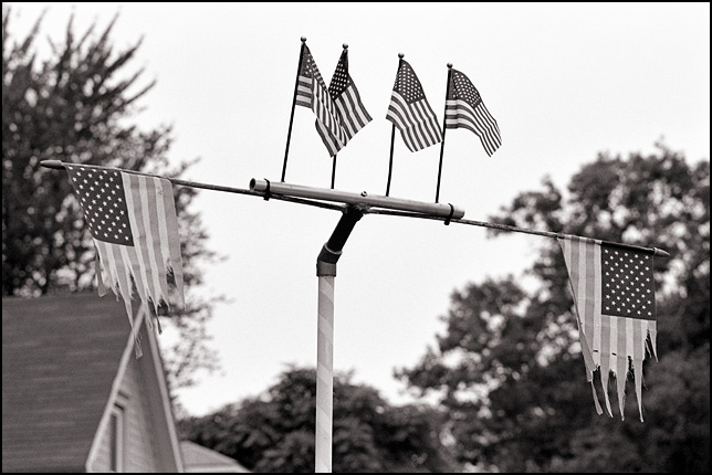 A cross-shaped flagpole with four small American flags on top and a tattered, faded flag on the end of each arm. It is on the corner of Oak Street and Lincoln Highway in the small town of New Haven, Indiana. An old house is visible in the background.