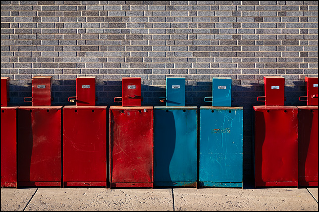 A collection of old blue and red newspaper vending machines facing a gray brick wall in front of the Fort Wayne Newspapers building on Main Street in downtown Fort Wayne, Indiana.