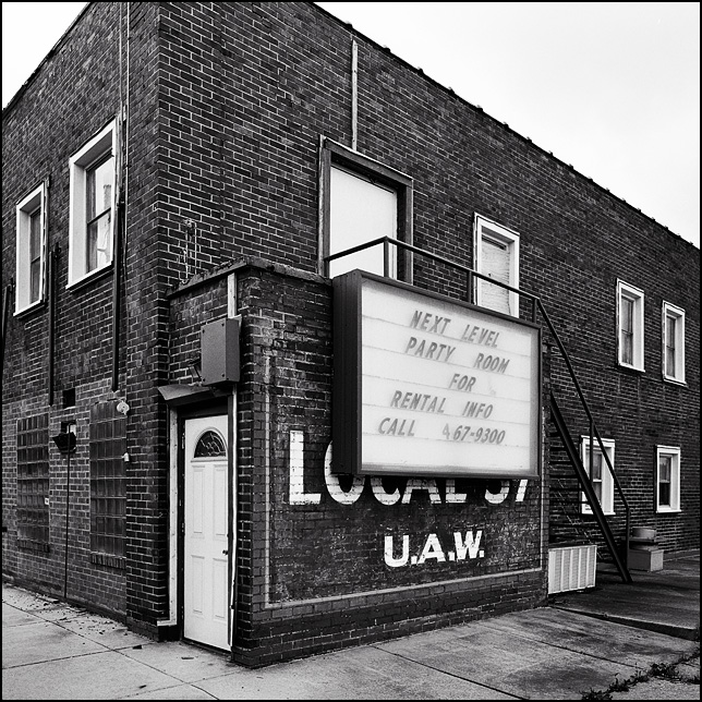 An old brick building with a United Auto Workers union hall sign painted on it, under a modern sign for a reception hall called Next Level Party Room. It is on South Coliseum Boulevard in Fort Wayne, Indiana.