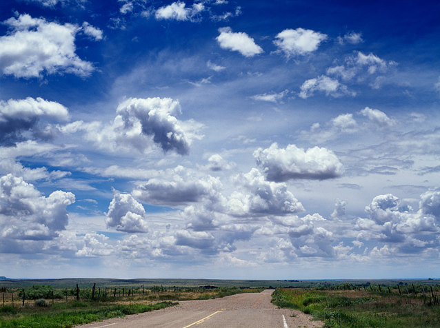 A landscape scene where the pavement ends and a dirt road begins under a deep blue sky with dramatic clouds along old route 66 in Quay County, New Mexico.