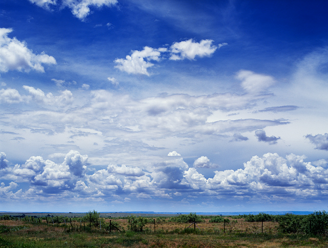 A landscape scene with deep blue sky and big clouds along old route 66 in Quay County, New Mexico.