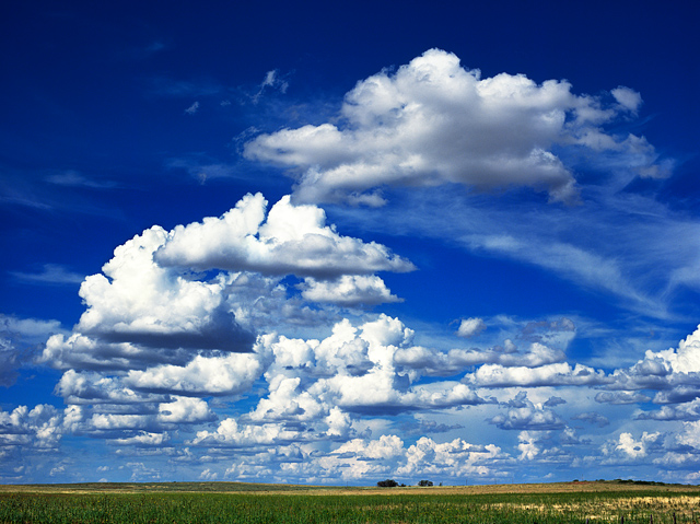 A dramatic blue sky and big clouds over the green plains along Interstate 40 in Quay County, New Mexico just east of the town of Bard.