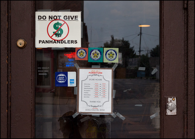 Do Not Give Money To Panhandlers, a sign on the door of a business on Wells Street in Fort Wayne, Indiana.