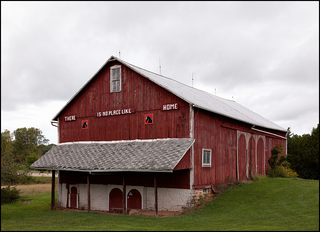 An old red barn on a farm in rural Indiana with a sign that says There Is No Place Like Home.