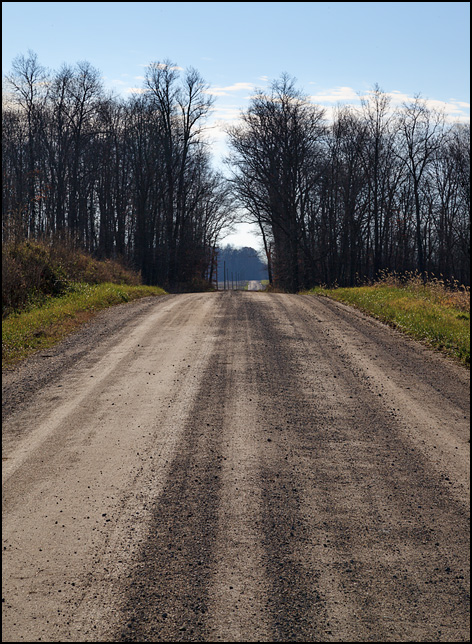 County Road 250W, a gravel country road, stretches out into the distance over a hill and through a forest in rural Noble County, Indiana. This view of the road looks south from a spot between County Road 275S and County Road 400S.