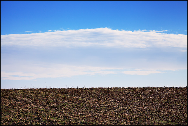 A mountain of thin transparent white clouds in a pale blue sky looms over a harvested cornfield on County Road 250W in rural Noble County, Indiana.