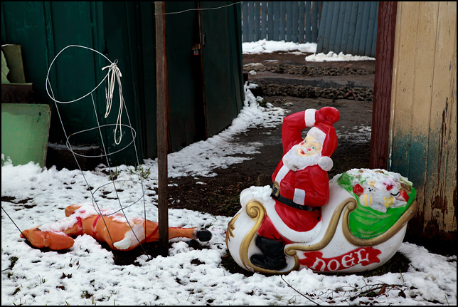 A plastic Santa and reindeer holiday decoration discarded behind a toolshed and covered in snow a month after Christmas.