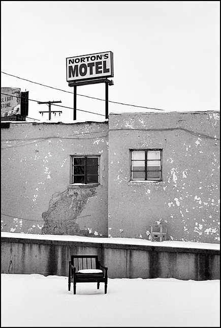 An empty chair sits in the snow next to Nortons Motel under the arrow sign that stands over this abandoned hotel on Maumee Avenue on the east side of Fort Wayne, Indiana.