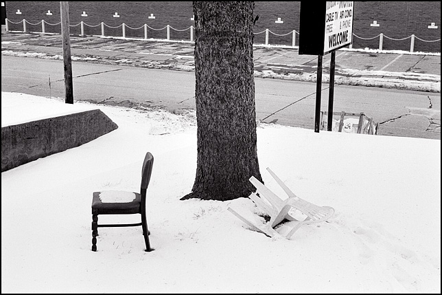 A wooden dinette chair and a plastic patio chair sit in the snow under a tree in front of Nortons Motel, an abandoned hotel on Maumee Avenue in Fort Wayne, Indiana. The welcome sign is visible in the background by the road.