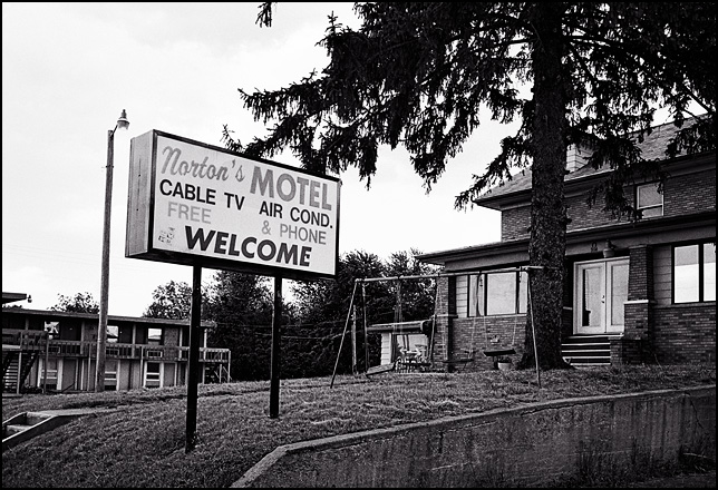 A swing set and the sign for Norton's Motel stand in the front yard of the old brick house on the hill next to the abandoned hotel in Fort Wayne, Indiana.