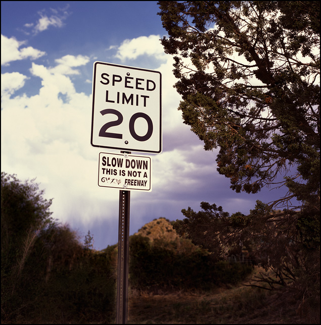 A sign that says to slow down hangs under a speed limit sign in the hills near Cerrillos, New Mexico.
