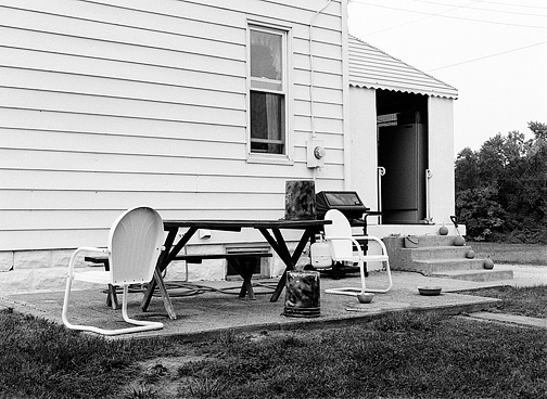 A pair of white metal motel chairs and a picnic table with pumpkins on the back porch of a farmhouse on Bass Road in Allen County, Indiana.