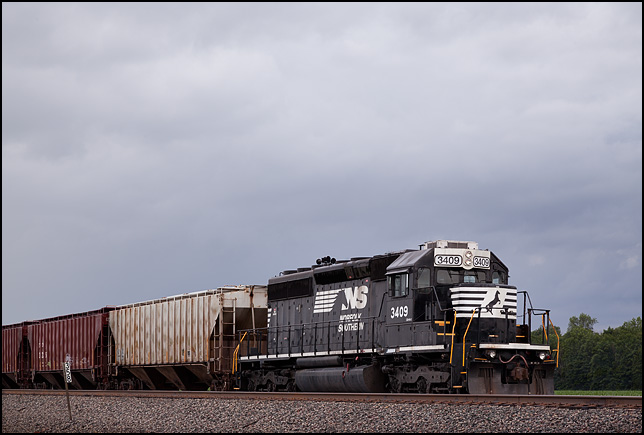 A Norfolk Southern diesel locomotive pulling a freight train on a rainy evening in rural Allen County, Indiana.