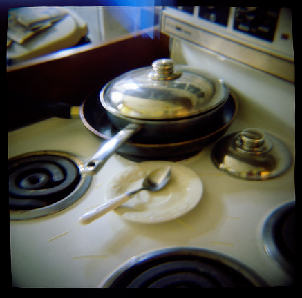 A stack of pans with a dirty plate and spoon on a stove with dried spaghetti scattered all over it, photographed with a Diana toy camera.