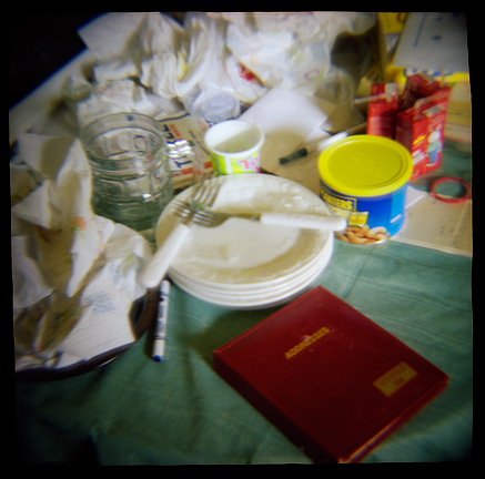 Dirty dishes and a red address book on the kitchen table, photographed with a Diana toy camera.