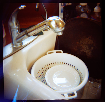 A colander with a white plate and a round pizza pan sit in the kitchen sink, photographed with a Diana toy camera.