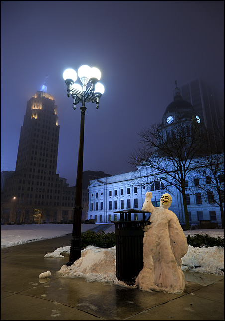 A snowman wearing a Guy Fawkes mask stands next to a streetlight in front of the Allen County Courthouse in downtown Fort Wayne. It was built by Occupy Fort Wayne members.