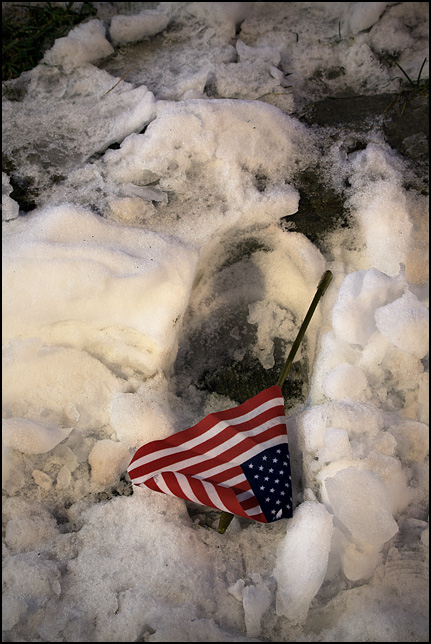 A small American flag in the snow on a sidewalk near the courthouse in Fort Wayne, Indiana.