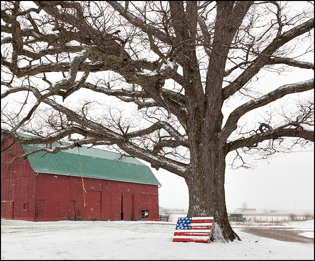 An American flag pallet leaned against a large tree in front of a red barn during a snowstorm. Located on O'Day Road in rural northwest Allen County, Indiana.