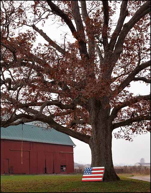 An American flag pallet leaned against a large tree in front of a red barn on a hazy morning at a farm on O'Day Road in rural northwest Allen County, Indiana.