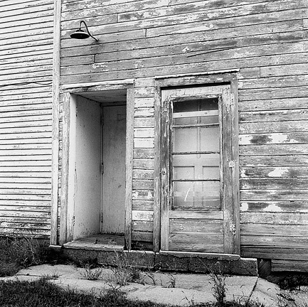 Two doors and a light on the side of the Odd Fellows Hall in Dunfee, Indiana. The siding on the building is covered in peeling paint.
