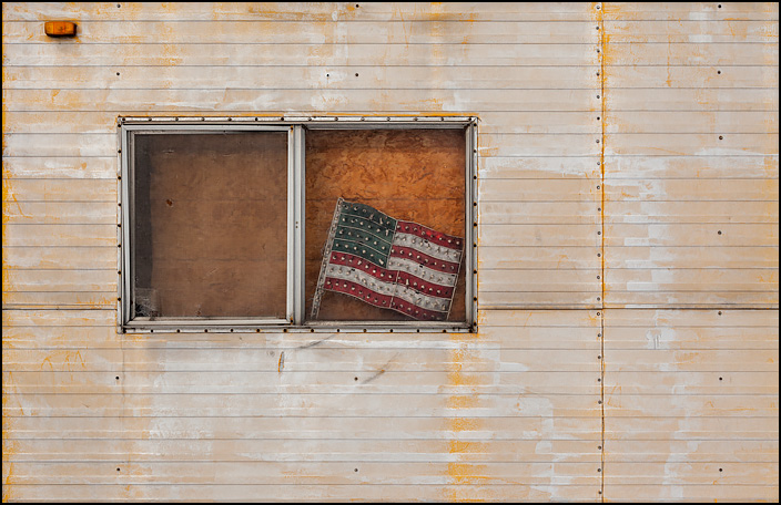 A lighted American flag decoration in the window of an abandoned trailer. Many of the tiny light bulbs on the flag are broken or torn out.