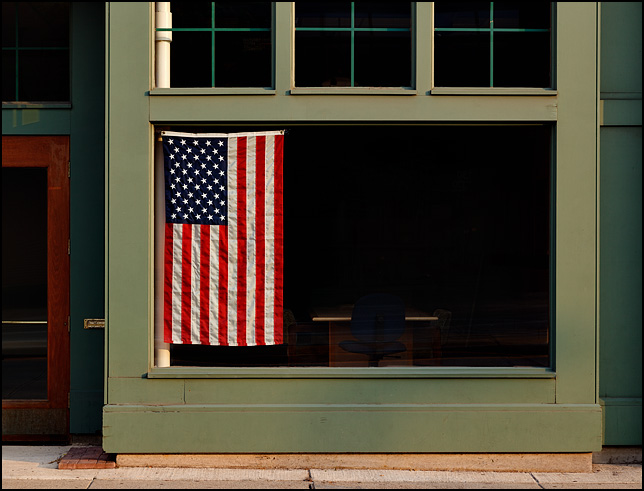 A large American flag in the front window of an office on Main Street in Fort Wayne, Indiana.