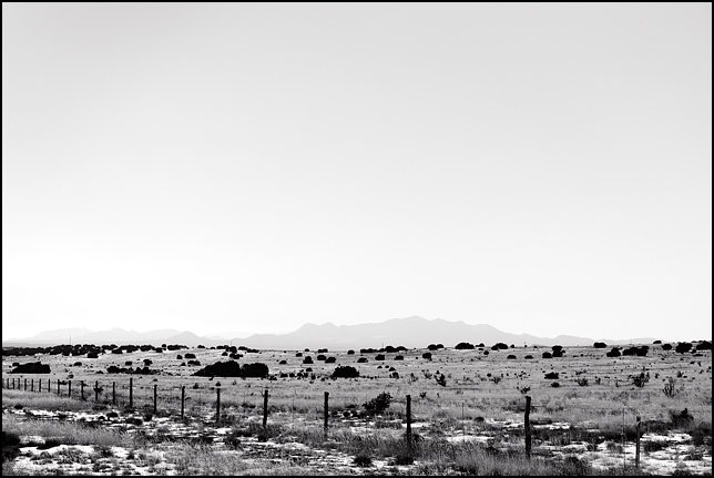 The open pasture of the Galisteo Basin stretches back to the horizon toward the Ortiz Mountains in New Mexico.