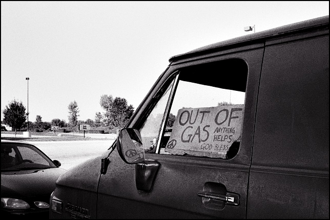 A cardboard sign in the window of an old van that says Out of Gas, anything helps, God Bless. The sign has the peace symbol drawn on it.