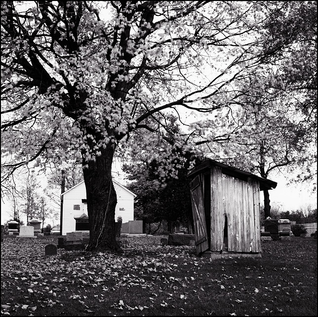 The old dilapidated outhouse in the Prairie Grove Cemetery in the Waynedale section of Fort Wayne, Indiana. The old white wooden chapel can be seen in the background and a tree stands next to the outhouse, which is surrounded by fall leaves.