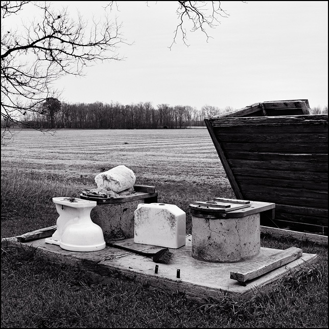 An two-seater outhouse that has been overturned, revealing the two seats that stick up from the concrete floor. An old toilet sits in front of one of the otuhouse holes.