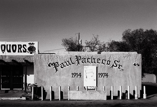 Owl's Liquors on Saint Francis Drive in Santa Fe, New Mexico. A Memorial to Paul Pacheco Senior is painted in Spanish gothic lettering on the front of the pueblo style adobe building, and a shopping cart full of cardboard boxes is wedged behind a cement pedestal in front of the store.