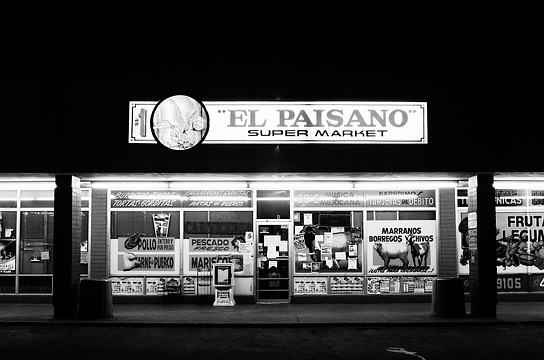 El Paisano Mexican supermarket in Santa Fe, New Mexico. Photographed at night. The signs in the windows glow with advertisements for musica, fruita, and la panaderia.