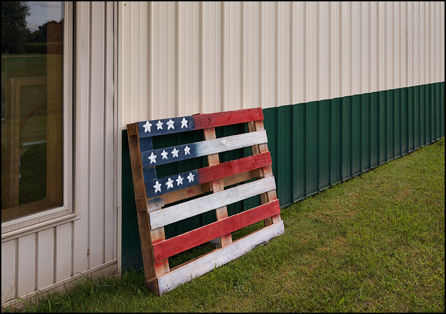 An old wooden pallet with an American flag painted on it leaned against a steel industrial building.
