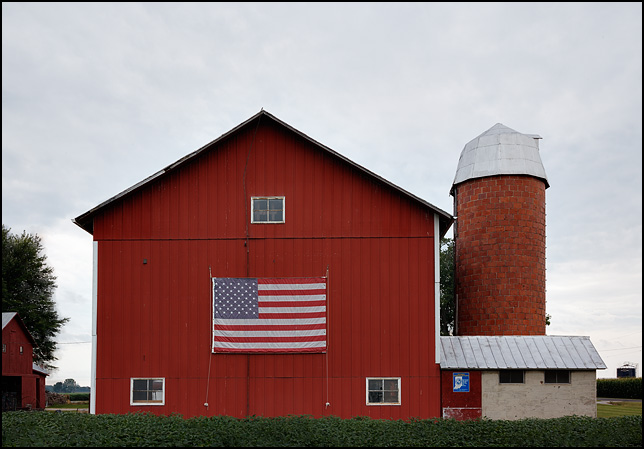 A large American Flag on the side of a red barn at a Hoosier Homestead Farm on Parent Road in Allen County, Indiana.