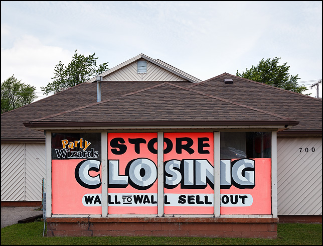 Store Closing signs cover the windows of Party Wizards, a locally owned retailer in Muncie, Indiana.