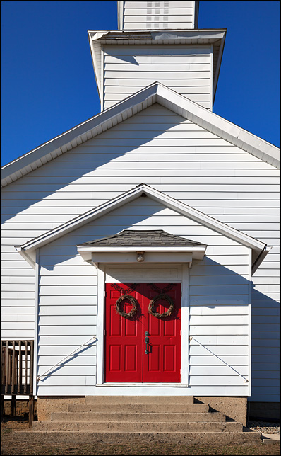 Bright red doors on the front of an old white church in rural Dekalb County, Indiana. Path of Life Community Church on State Road 327.