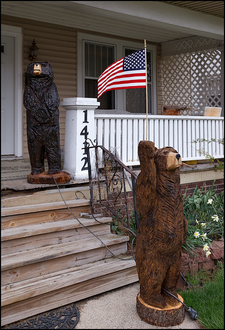 A chainsaw sculpture of a bear carved from a large log stands in front of a house holding an American flag.