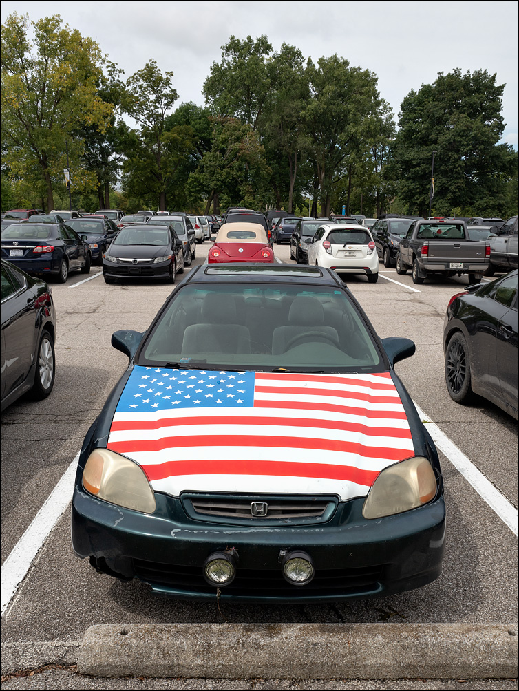 An old Honda car with the hood painted as the American flag sits in a parking lot at Purdue Fort Wayne in Fort Wayne, Indiana.