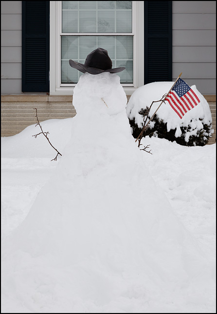 A patriotic snowman holding an American flag in front of a house in the Waynedale area of Fort Wayne, Indiana.