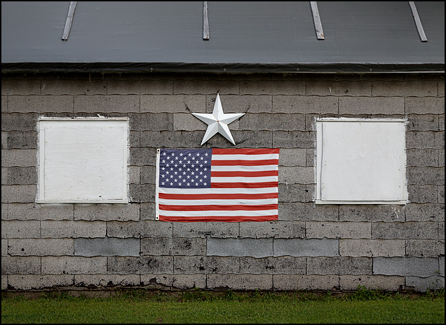 An American flag and a big silver star hang between boarded-up windows on the side of an old garage on Paul Street in Fort Wayne, Indiana.