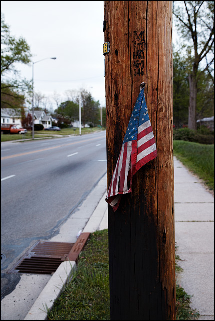A dirty and torn American flag nailed to a utility pole in an inner-city neighborhood.