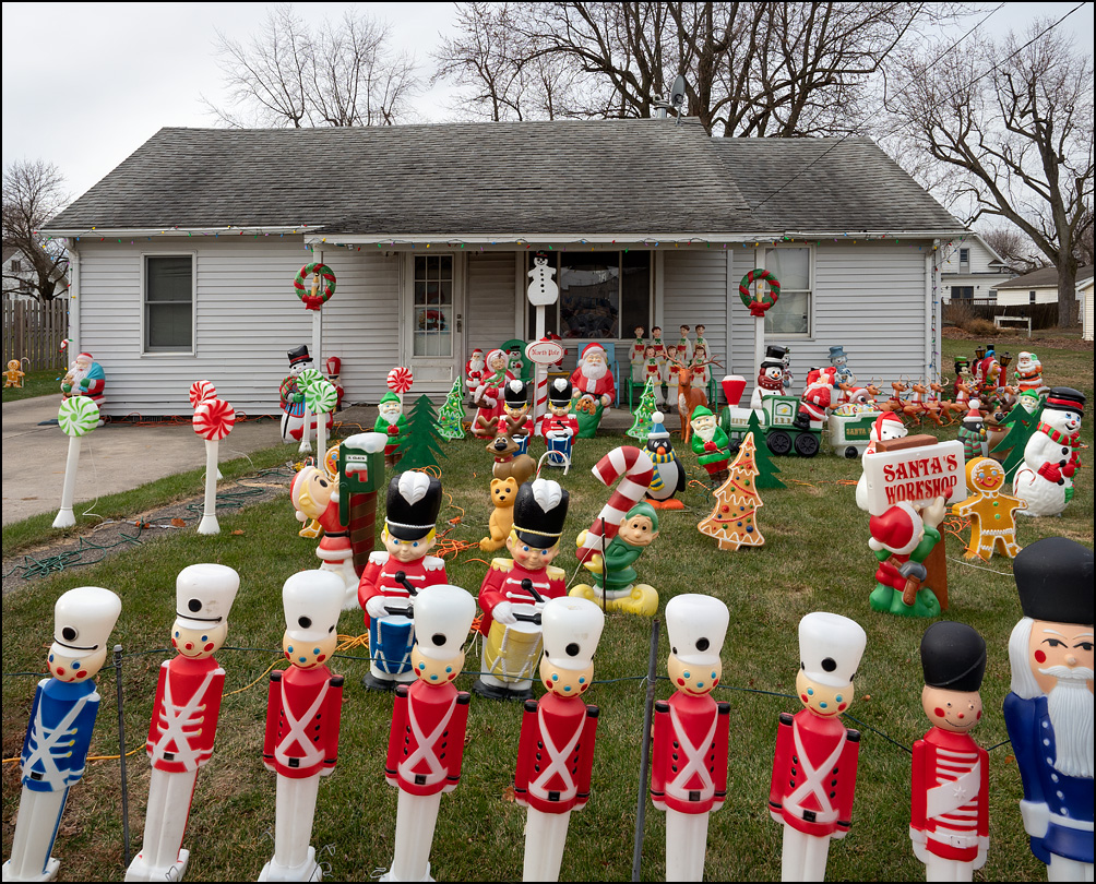 Plastic Christmas decorations fill the front yard of a house on Laura Street in the small town of Payne, Ohio. The decorations include nutcracker toy soldiers, Santa Claus, snowmen, elves, Christmas trees, candy canes, wreaths, a Santa Train, and gingerbread men.
