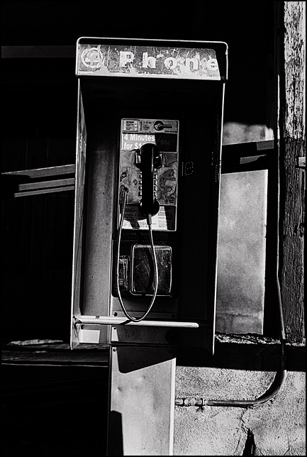 An old payphone in front of a store in the tiny former mining town of Cerrillos, New Mexico. The phone is a modern style pay phone but it is beat up and vandalized.